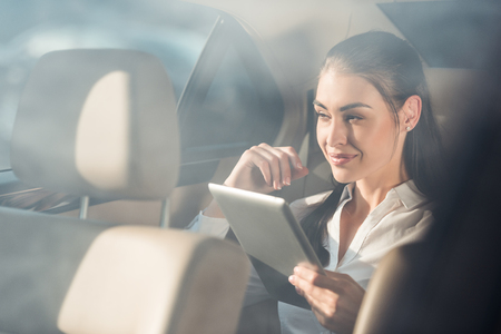 Young attractive woman sitting in a backseat of a car and using her digital tablet