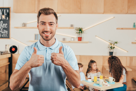 young man showing thumbs up with his family blurred on background Stock Photo - 102355479