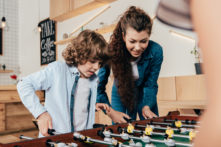 portait of happy mother and son playing table footbal