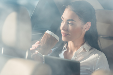 Young attractive woman sitting in a backseat of a car with digital tablet and cup of coffee Stock Photo