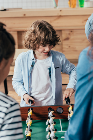 little boy playing table football with his family