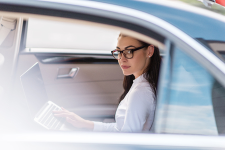 Young woman in glasses sitting in a backseat of a car with laptop and looking at camera