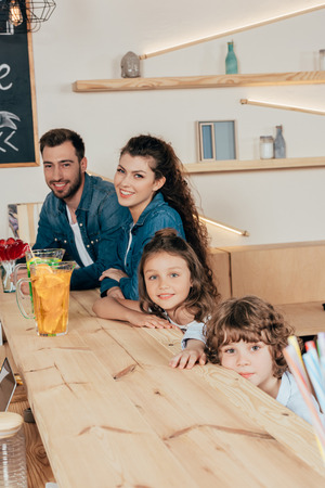 cheerful young family in cafe at bar counter