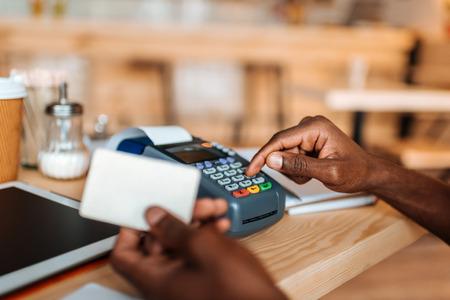 Vue recadrée du propriétaire afro-américain travaillant avec une carte de crédit et un terminal dans un café