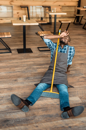 tired african american man resting on floor after brooming in coffee shop