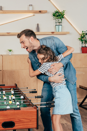 father and daughter celebrating win in table football