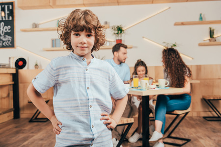 cute curly boy in cafe with his happy family blurred on background