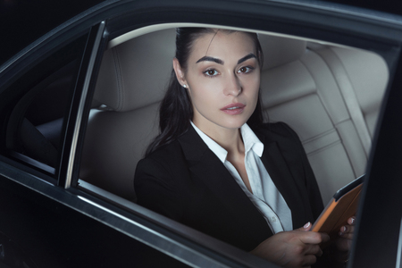 Young charming woman in suit  sitting in backseat of car with digital tablet