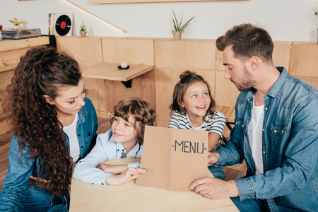 beautiful young family with menu list in cafe