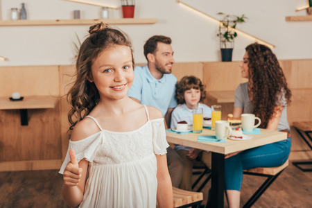 little girl showing thumb up in cafe with her happy family blurred on background Stock Photo