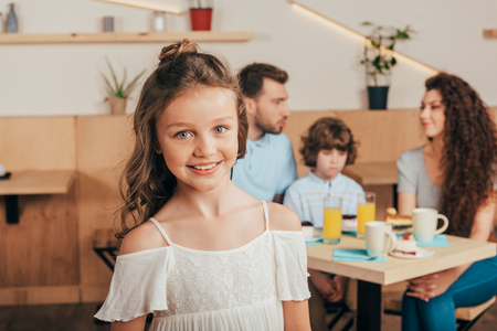 cheerful little girl in cafe with her happy family blurred on background Stock Photo