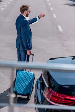 businessman in suit with suitcase for business trip at car