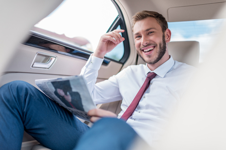 happy young man with newspaper on backseat of car