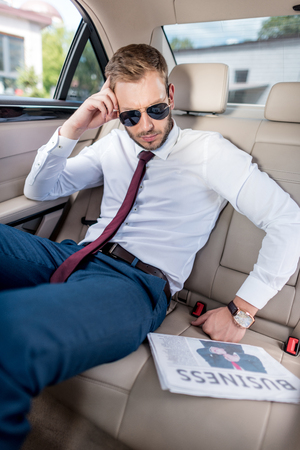 young stylish businessman in sunglasses with business newspaper on backseat of car Stock Photo