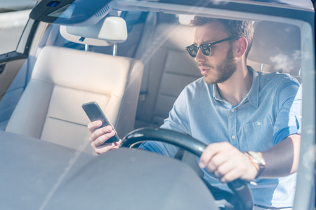 young man in sunglasses using smartphone while driving car