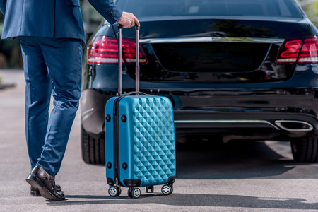cropped view of businessman in suit with suitcase for business trip at car
