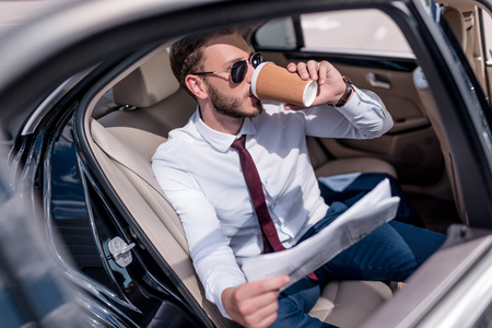 young stylish businessman in sunglasses with newspaper drinking coffee on backseat of car
