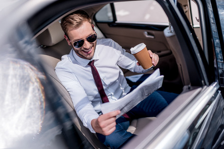 smiling stylish businessman in sunglasses with coffee and newspaper on backseat of car Stock Photo
