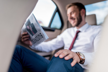 selective focus of young man reading newspaper on backseat of car