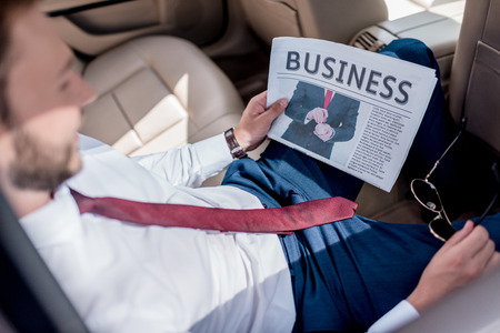 selective focus of man reading business newspaper on backseat of car Stock Photo