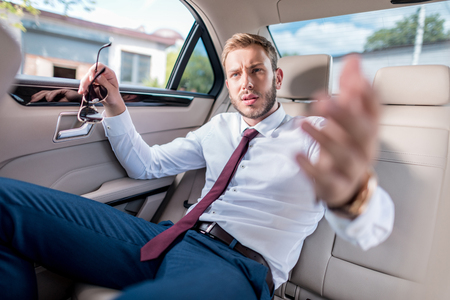 young stylish businessman with sunglasses on backseat of car