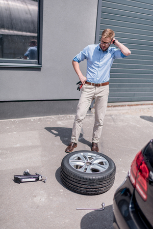 young handsome man changing car tire  Stok Fotoğraf