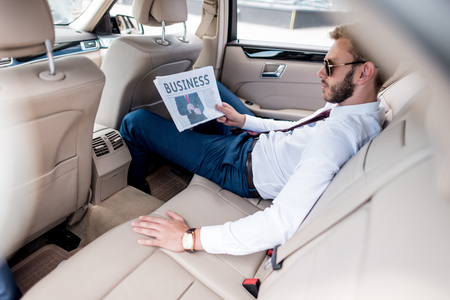 young stylish businessman in sunglasses reading business newspaper on backseat of car