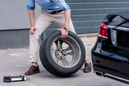 low section of young man changing car tire