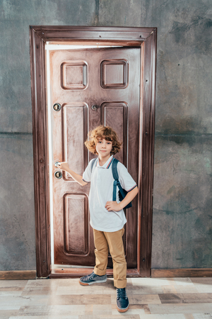 cute little boy going to school, standing next to door Stock fotó