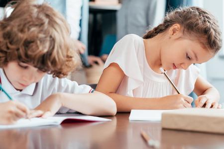 pensive little kids doing homework together