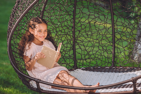 smiling african american girl reading book while sitting in swinging hanging chair in park