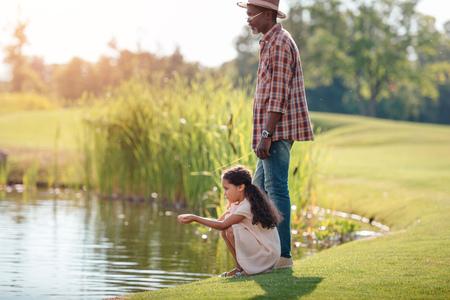 petite-fille afro-américaine et son grand-père debout ensemble près du lac dans le parc