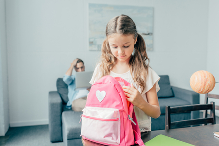 cute little girl preparing backpack for school Stock Photo
