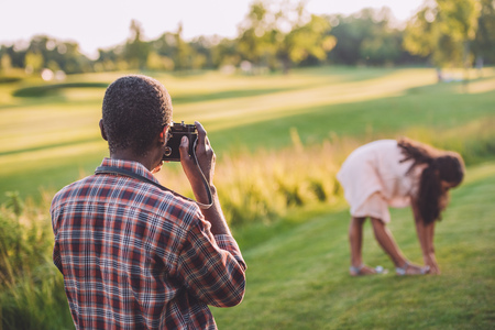 african american man taking photo of his granddaughter playing on green lawn 写真素材 - 102893997