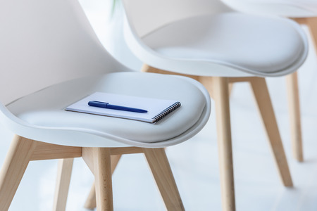 Notepad and pen on chair in modern office