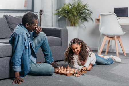 Cute african american girl playing chess with father on floor at home Banque d'images - 103198619