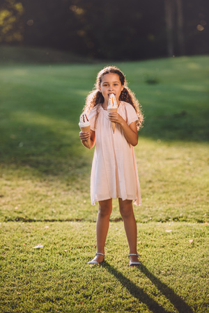 happy african american girl eating ice cream in cones while standing in park in sunlight Stock Photo