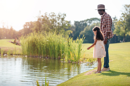 african american granddaughter and her grandfather standing together near lake in park Banque d'images - 102355650