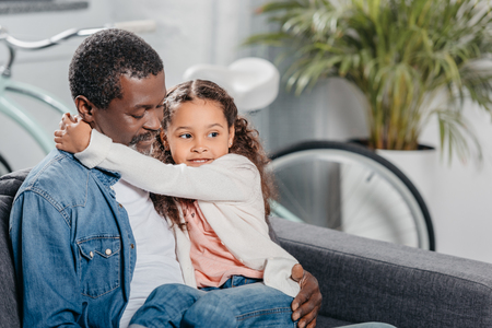 Adorable african american girl hugging father while they sitting on sofa at home