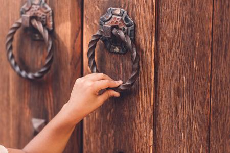Vue recadrée de l'enfant frapper à la porte avec poignée en métal