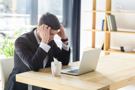 Young businessman suffers from headache while working on laptop Stock fotó