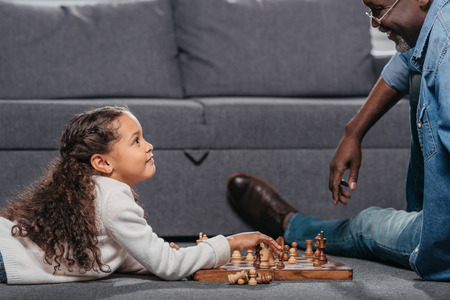Cute african american girl playing chess with father on floor at home Stock Photo