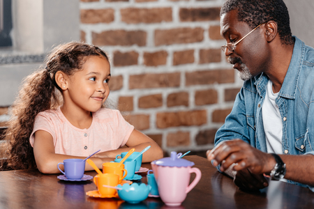 African american girl having tea party with father at home Foto de archivo - 102894066