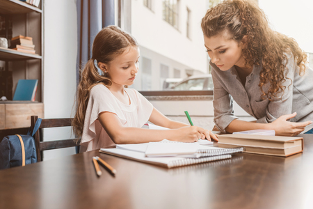 beautiful young mother and daughter doing homework together