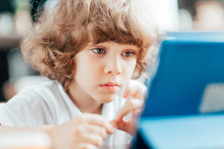beautiful curly kid looking at digital tablet