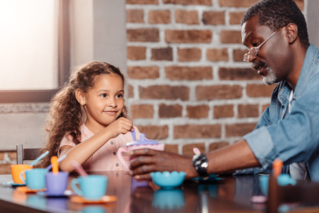 African american girl having tea party with father at home Stock Photo