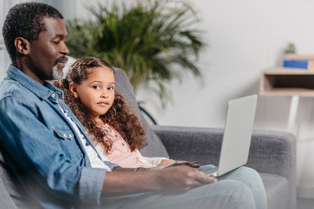 adorable african american girl using laptop together with father at home 免版税图像