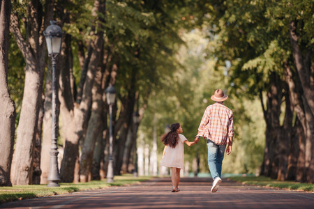 back view of african american girl holding hands with grandfather and walking in park Stock fotó