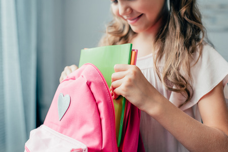 cropped shot of girl preparing backpack for school
