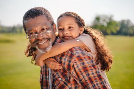 Heureuse petite-fille afro-américaine étreignant son grand-père souriant sur pelouse verte